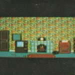 Possibly different wall paper - hard to tell.  There is something on the carpet, and an odd rectangle above the telly.